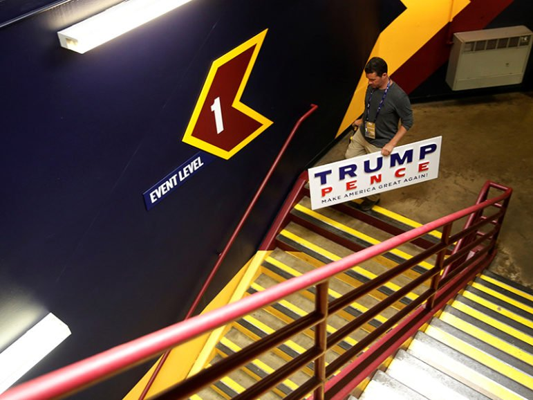 A worker walks with a Trump-Pence campaign sign in an arena stairwell as preparations continue on the floor of the Republican National Convention in Cleveland on July 17, 2016. Photo courtesy of REUTERS/Jonathan Ernst *Editors: This photo may only be republished with RNS-GEHRING-OPED, originally transmitted on July 20, 2016.