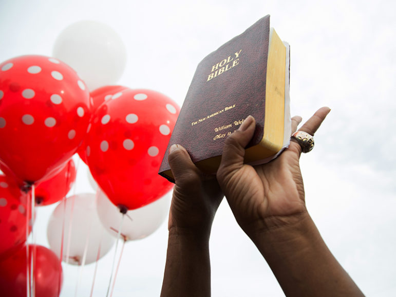 A community member holds up a Bible during a vigil in memory of Alton Sterling, who was shot dead by police at the Triple S Food Mart in Baton Rouge, La., on July 6, 2016. Photo courtesy of REUTERS/Jeffrey Dubinsky *Editors: This photo may only be republished with RNS-GUSHEE-OPED, originally transmitted on July 7, 2016.