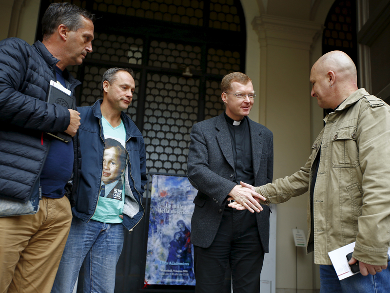 """Father Hans Zollner (2nd R) greets Andrew Collins, David Ridsdale (L) and Peter Blenkiron (2nd L), who said they were child sex abuse victims, at the end of a meeting at the Gregoriana University in Rome, on March 3, 2016. Cardinal George Pell said he should have done more to stop the sexual abuse of children in the Catholic Church, acknowledging that he was told of at least one priest """"misbehaving"""" with boys at an Australian school. Photo courtesy of REUTERS/Tony Gentile"""