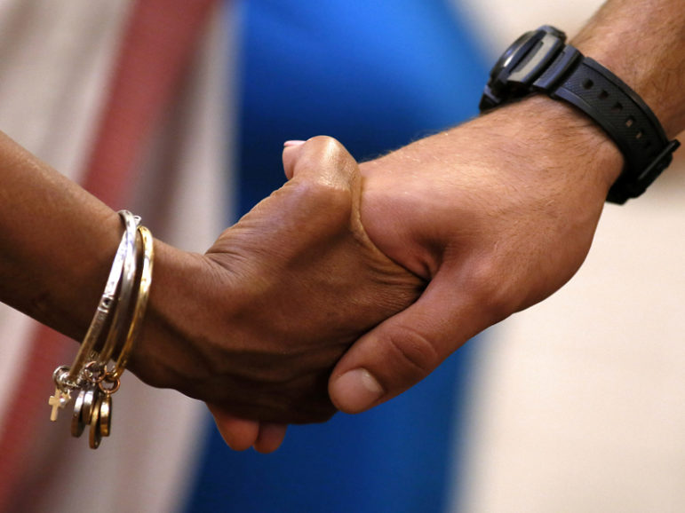 A man and a woman hold hands in prayer during a