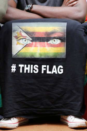 A supporter of Zimbabwean Pastor Evan Mawarire's displays t-shirt with a flag as he sits outside the Harare Magistrates court during Mawarire's trial, on July 13, 2016. Photo courtesy of REUTERS/Philimon Bulawayo *Editors: This photo may only be republished with RNS-ZIMBABWE-PASTOR, originally transmitted on July 21, 2016.