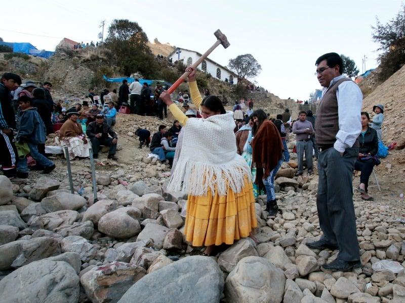 An Aymara woman tries to break a rock with a sledge hammer