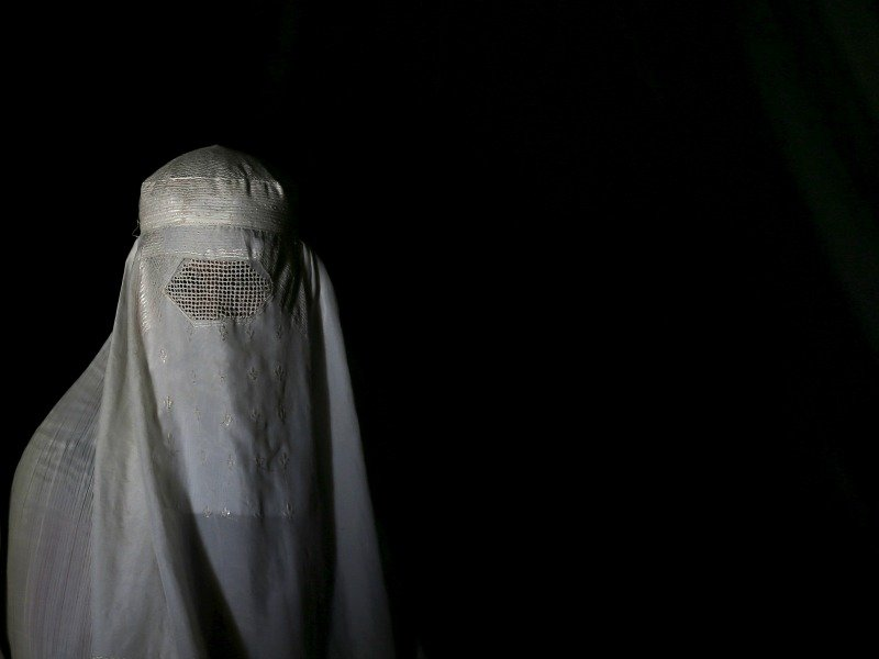 An Afghan refugee woman, clad in a burqa