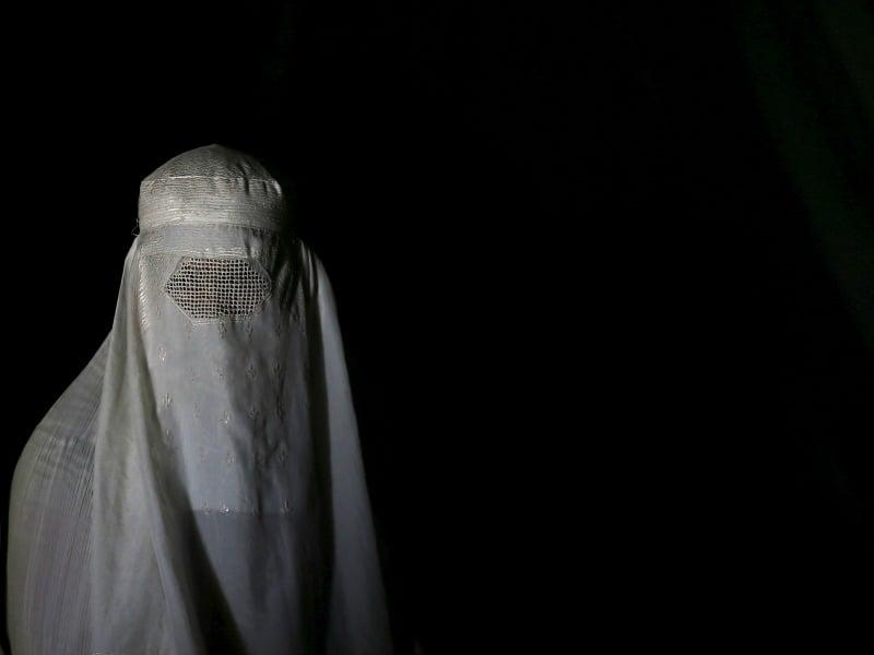 An Afghan refugee woman, clad in a burqa