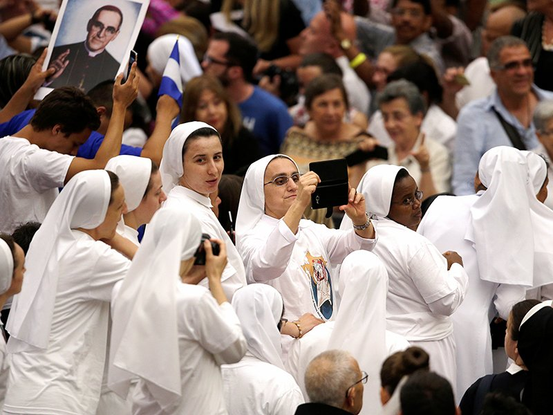 Nuns take pictures as the wait for the arrival of Pope Francis to lead the weekly audience in Paul VI hall at the Vatican