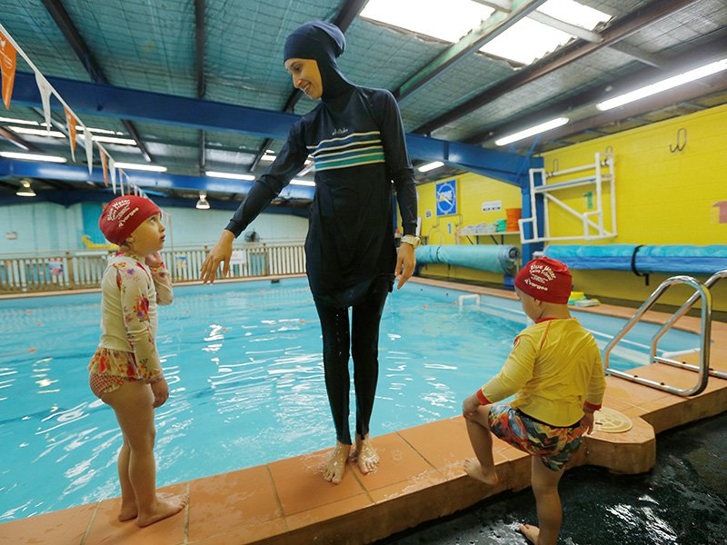 Australian muslim swimming instructor Fadila Chafic wears her full-length 'burkini' swimsuit during a swimming lesson with her children Taaleenand Ibrahim at swimming pool in Sydney