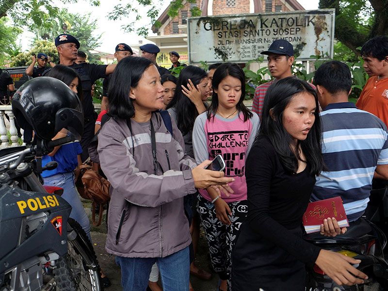 People are seen outside Saint Joseph catholic church following a suspected terror attack by a knife-wielding assailant on a priest during the Sunday service in Medan, North Sumatra, Indonesia