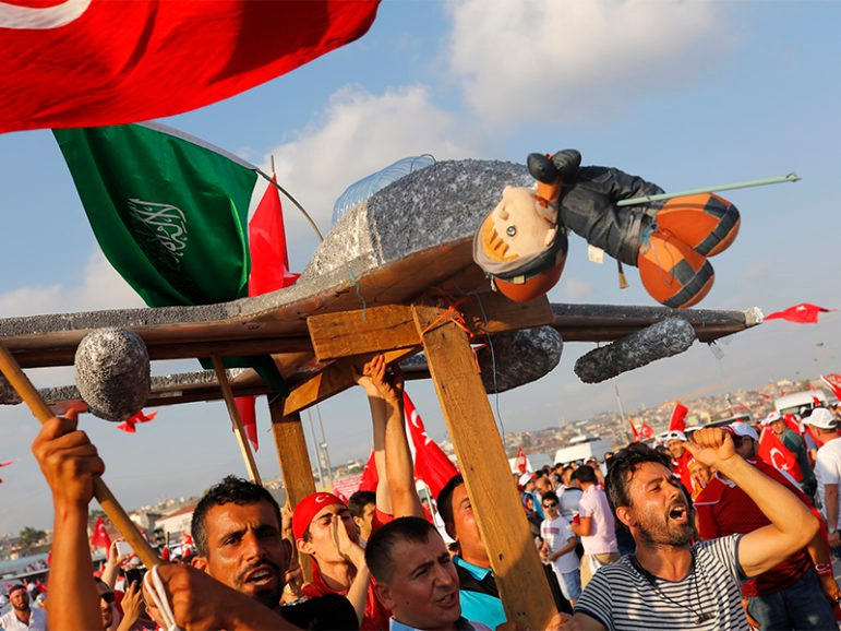 People hold a plane model with attached toy, depicting opposition cleric in exile Fethullah Gulen, during the Democracy and Martyrs Rally, organized by Turkish President Recep Tayyip Erdogan and supported by ruling AK Party (AKP), oppositions Republican People's Party (CHP) and Nationalist Movement Party (MHP), to protest against last month's failed military coup attempt, in Istanbul, Turkey, on Aug. 7, 2016. Photo by Umit Bektas/Reuters