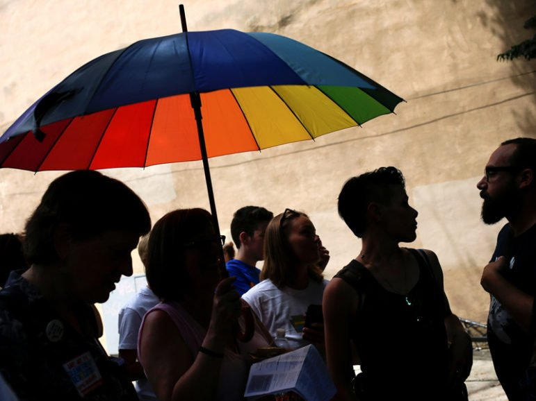 Activists stand under an umbrella in the colors of the LGBT pride flag as they take part in a protest against Westboro Baptist Church members demonstrating nearby in downtown during the 2016 Democratic National Convention in Philadelphia on July 26, 2016. Photo courtesy of REUTERS/Adrees Latif *Editors: This photo may only be republished with RNS-GUSHEE-OPED, originally transmitted on August 23, 2016.