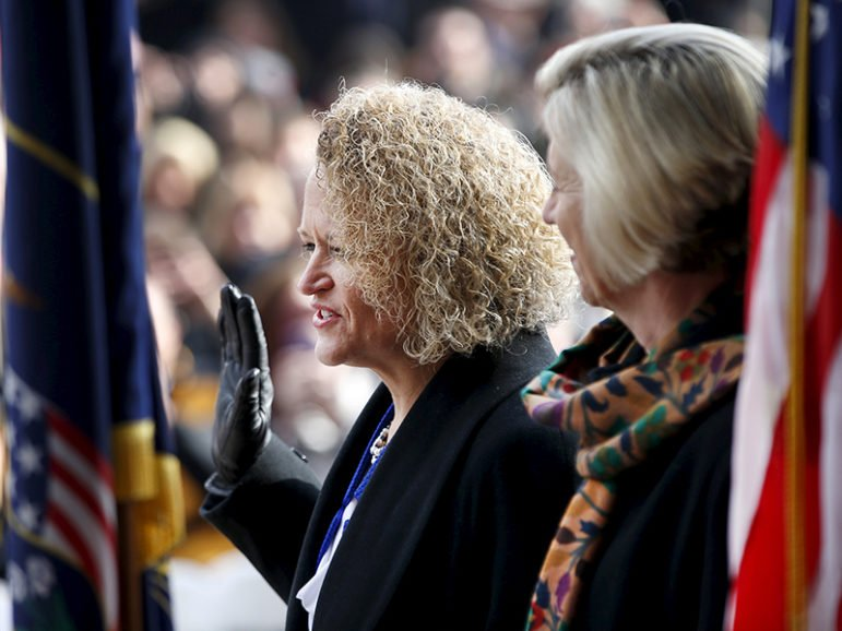 Jackie Biskupski, left, is sworn in as Salt Lake City's mayor as her fiancee, Betty Iverson, watches on Jan. 4, 2016. The former state lawmaker is the first openly gay person to hold the office. Photo courtesy of REUTERS/George Frey