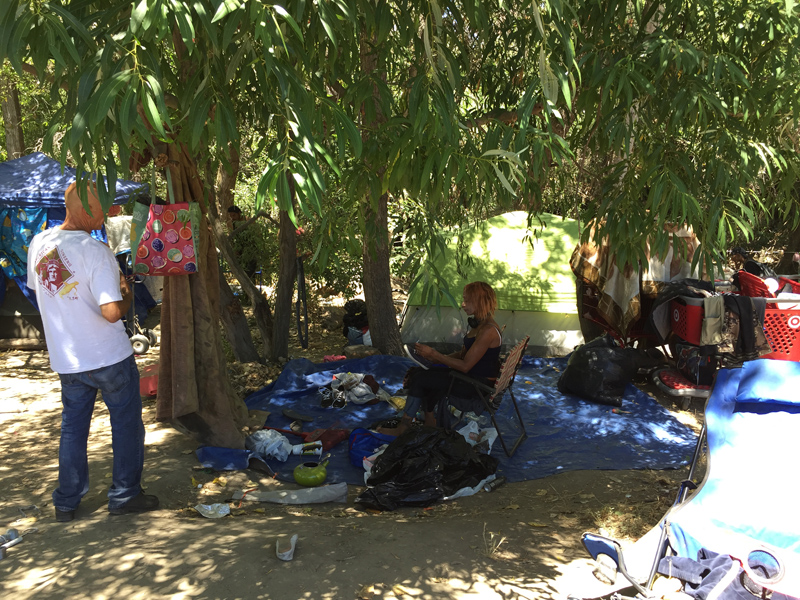 A group of homeless people gather in a clearing beside Coyote Creek in San Jose. RNS photo by Yonat Shimron