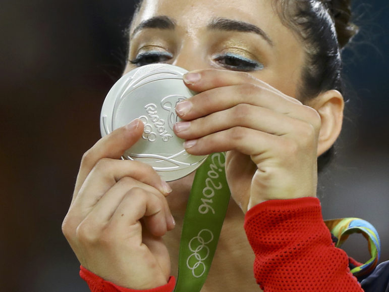 Aly Raisman looks at her silver medal on the podium after the women's floor competition in Rio de Janeiro on August 16, 2016. Photo courtesy of REUTERS/Mike Blake  *Editors: This photo may only be republished with RNS-OLYMPICS-RAISMAN, originally transmitted on August 16, 2016.