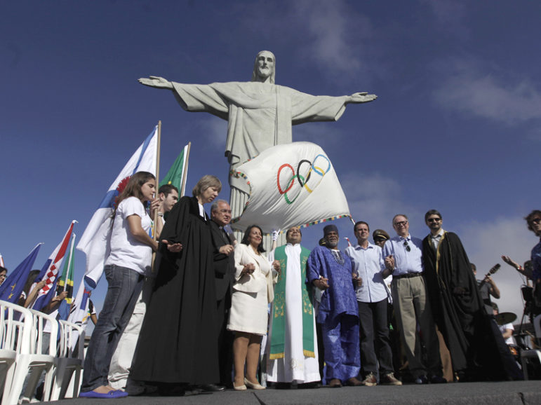 Rio de Janeiro's Mayor Eduardo Paes, in untucked dress shirt; Brazilian Olympic Committee President Carlos Arthur Nuzman, in khaki pants; and leaders of different religions pray next to the Olympic Flag in front of
