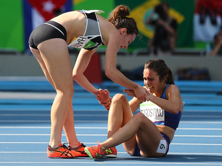 Nikki Hamblin, left, of New Zealand stops running during the race to help fellow competitor Abbey D'Agostino of the U.S. after D'Agostino suffered a cramp during the preliminary women's 5000m Round 1 in Rio de Janeiro on Aug. 16, 2016. Photo courtesy of REUTERS/Kai Pfaffenbach
