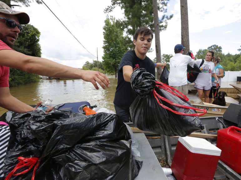A resident transfers his belongings into a boat after being rescued in Ascension Parish, Louisiana, on August 15, 2016. Photo courtesy of REUTERS/Jonathan Bachman  *Editors: This photo may only be republished with RNS-STETZER-OPED, originally transmitted on August 16, 2016.