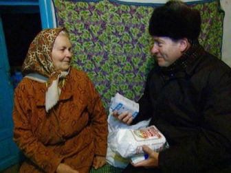 While visiting Holocaust survivors in Ukraine who are living in poverty in February 2016, Rabbi Yechiel Eckstein, right, brought food and heating supplies to Anna, plus words of encouragement and hope from The Fellowship's friends and supporters. Photo courtesy of JDC/Vladimir Shraga.