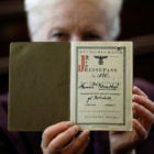 London rabbi Julia Neuberger poses for a photograph with the old German passport of her grandmother