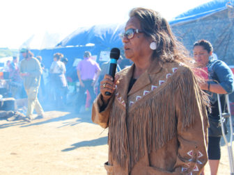 Phyllis Young, camp coordinator, speaks to those gathered at the Oceti Sakowin camp near Standing Rock Reservation in North Dakota after a prayer walk on Sept. 14, 2016, to the site up the road where Dakota Access began digging over Labor Day weekend for construction on a nearly 1,200-mile pipeline project. Construction temporarily has been halted. RNS photo by Emily McFarlan Miller