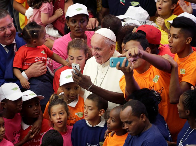 Pope Francis poses with refugees as he leads the weekly audience in Paul VI Hall at the Vatican on Aug. 3, 2016. Photo courtesy of Reuters/Max Rossi *Editors: This photo may only be republished with RNS-POPE-REFUGEE, originally transmitted on Sept. 20, 2016.