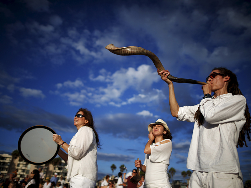 Jared Stein, right, blows a shofar as Rabbi Naomi Levy, left, plays a drum at the Nashuva Spiritual Community Jewish New Year celebration on Venice Beach in Los Angeles, Calif., on September 14, 2015. As Jews take part in the Tashlich prayer, a Rosh Hashanah ritual, bread crumbs are tossed into the waters to symbolically cast away sins. Photo courtesy of Reuters/Lucy Nicholson