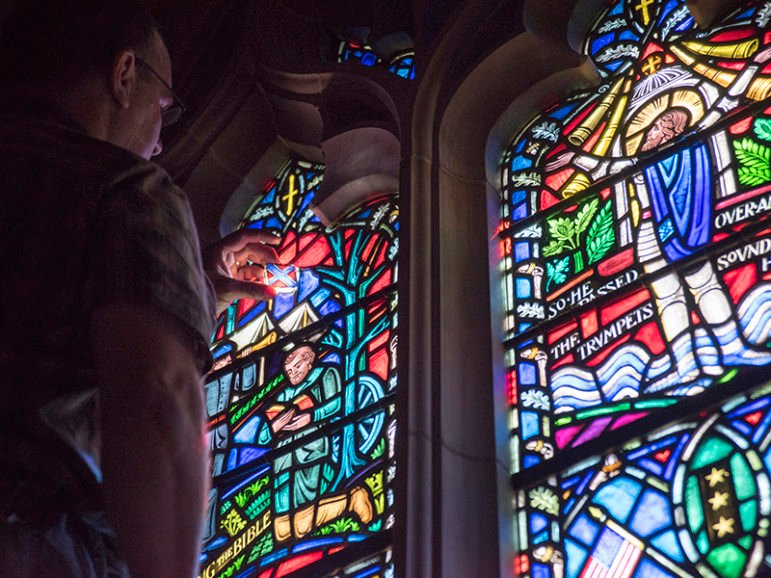 Andrew Goldkuhle of Goldkuhle Studios in Hanover, Va., inspects and replaces stained glass images of the Confederate battle flag at Washington National Cathedral. Photo courtesy of Danielle Thomas / Washington National Cathedral