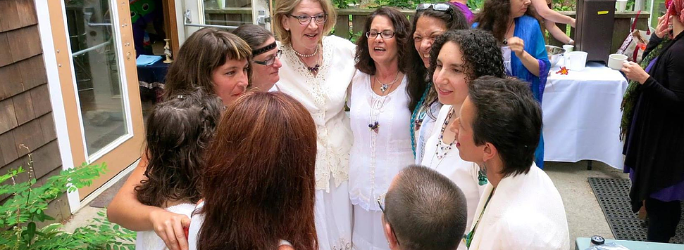 A group of women dressed in white for an ordination ceremony form a circle on the porch of the Isabella Freedman Retreat Center in Falls Village, Conn. Photo courtesy the Kohenet Hebrew Priestess Institute
