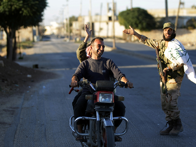 Residents driving a motorcycle gesture towards a fighter in Dabiq town, northern Aleppo countryside