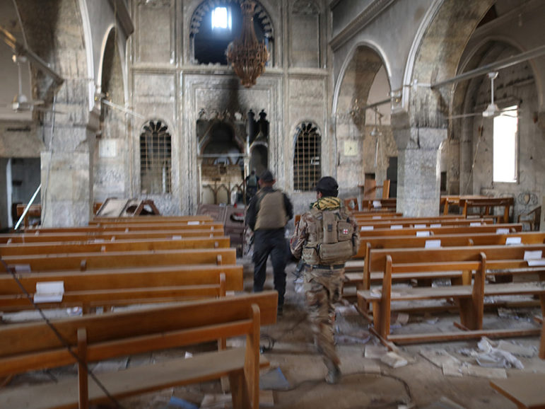 Iraqi special forces soldiers walk inside a church damaged by Islamic States fighters in Bartella, east of Mosul, Iraq