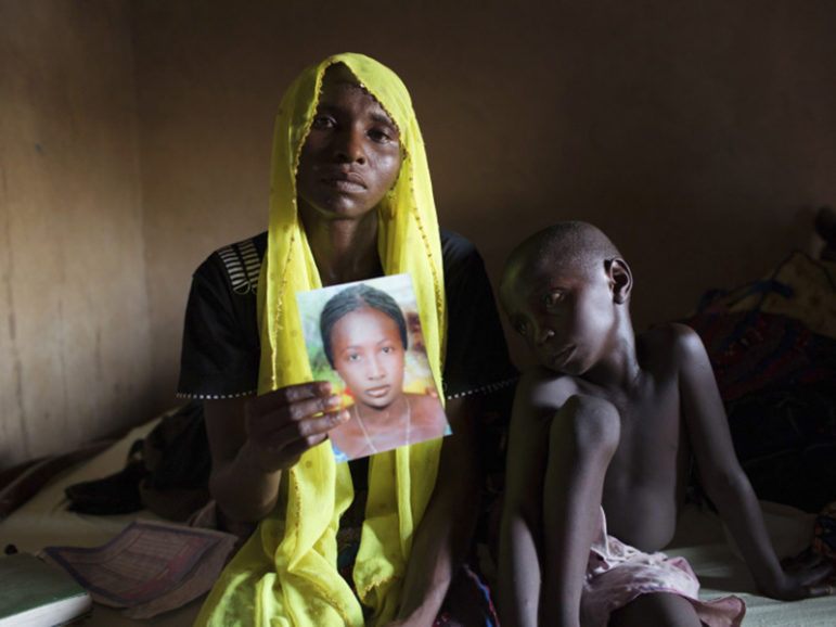 Rachel Daniel, 35, holds up a picture of her abducted daughter, Rose Daniel, 17, as Rachel's son Bukar, 7, sits beside her at her home in Maiduguri on May 21, 2014. Rose was abducted along with more than 200 of her classmates on April 14, 2014, by Boko Haram militants from a secondary school in Chibok, Borno state. Photo courtesy of REUTERS/Joe Penney