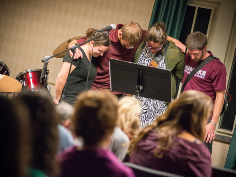 Students pray during an InterVarsity gathering at Roanoke College in Salem, Va.