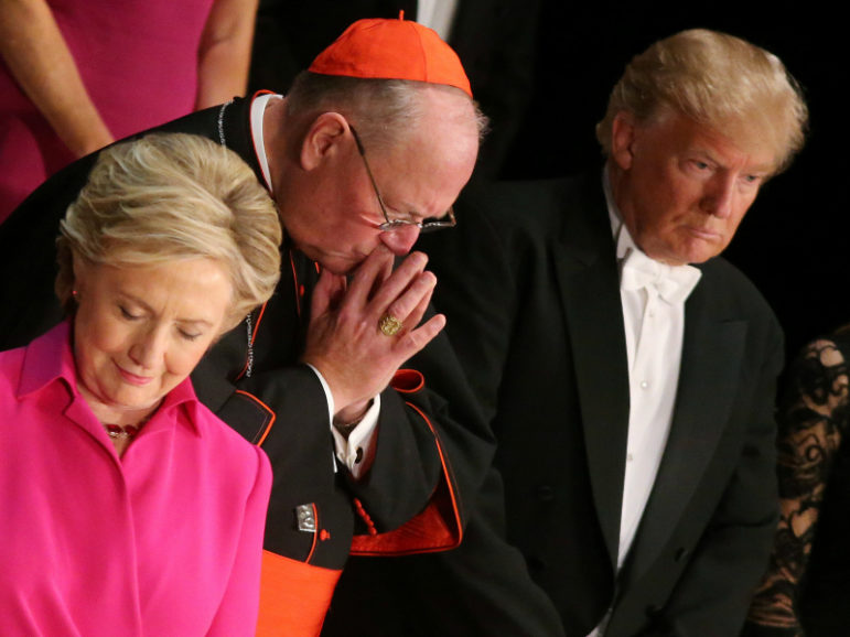 Democratic presidential nominee Hillary Clinton, Archbishop of New York Cardinal Timothy Dolan, and Republican presidential nominee Donald Trump pray as they attend the Alfred E. Smith Memorial Foundation dinner to benefit Catholic charities in New York.  October 20, 2016. Photo courtesy of Reuters/Carlos Barr