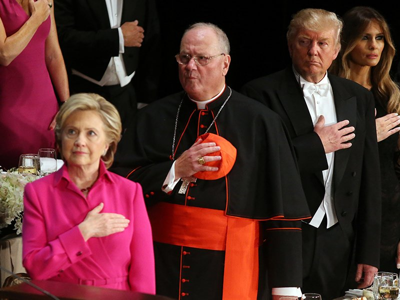 Republican U.S. presidential nominee Donald Trump looks at Democratic U.S. presidential nominee Hillary Clinton during the national anthem as they attend the Alfred E. Smith Memorial Foundation dinner to benefit Catholic charities in New York, on October 20, 2016. Photo courtesy of Reuters/Carlos Barria