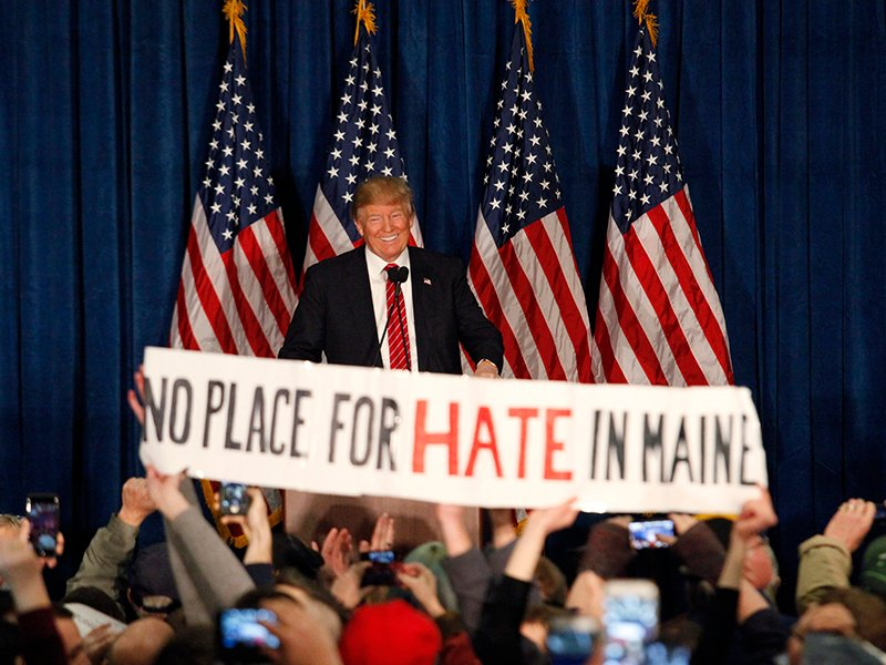 "Republican U.S. presidential candidate Donald Trump smiles as protestors hold up a sign reading ""No Place for Hate in Maine"" during a campaign rally in Portland, Maine on March 3, 2016. Photo courtesy of Reuters/Joel Page *Editors: This photo may only be republished with RNS-ANTI-SEMITISM, originally transmitted on Oct. 19, 2016."