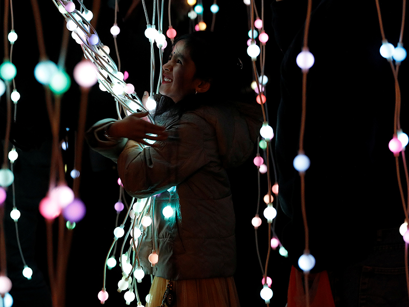 A girl plays in the ocean of lights attraction during the Diwali lights switch on in Leicester, Britain on October 16, 2016. Photo courtesy of Reuters/Darren Staples