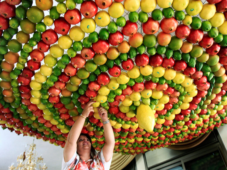 A woman from the Samaritan sect decorates with fruits and vegetables a traditional hut known as a