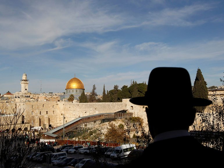 An ultra-Orthodox Jewish man stands at a point overlooking a wooden ramp leading up from Judaism's Western Wall to the sacred compound known to Muslims as the Noble Sanctuary and to Jews as Temple Mount, where the Al-Aqsa Mosque and the Dome of the Rock shrine stand, in Jerusalem's Old City on Dec. 12, 2011. Photo courtesy of Reuters/Ronen Zvulun