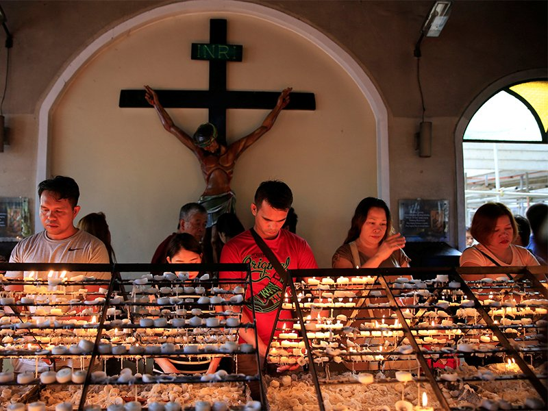 Filipino Catholic Devotees Light Candles And Offer Prayers After Attending A Mass At National Shrine Of Our Mother Perpetual Help In Baclaran