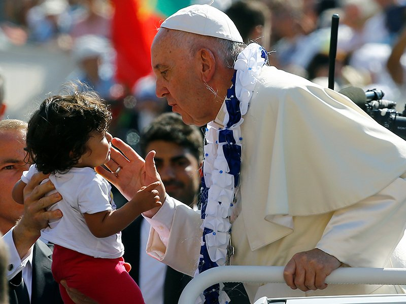 Pope Francis interacts with a child as he arrives for the audience for workers and volunteers of mercy at the Vatican, on September 3, 2016. Photo courtesy of Reuters/Stefano Rellandini *Editors: This photo may only be republished with RNS-POPE-MIGRANTS, originally transmitted on October 13, 2016.