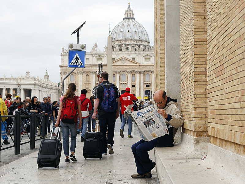 A man reads a newspaper in front of St. Peter Square at the Vatican on April 8, 2016. Photo courtesy of Reuters/Alessandro Bianchi *Editors: This photo may only be republished with RNS-VATICAN-DYLAN, originally transmitted on October 13, 2016.