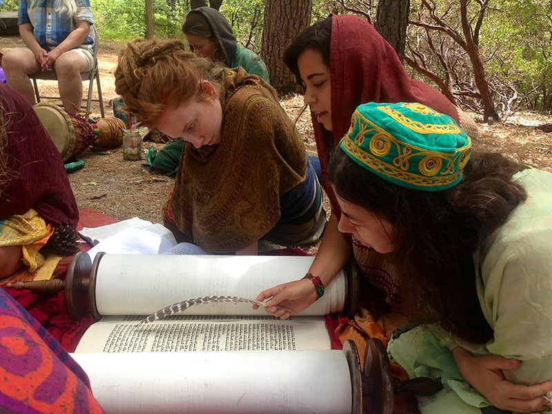 Yael Schonzeit chants from the Torah during a Kohenet training week this past July in Northern California, while Kohenet co-founder Rabbi Jill Hammer and student Sarah Moser look on. Photo courtesy of Kohenet Hebrew Priestess Institute