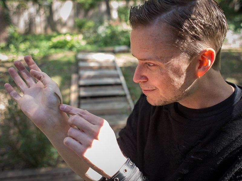 Lucien Greaves, spokesperson and co-founder of the Satanic Temple, finds a caterpiller in the backyard of a friend's home in Lenexa, Kan., on September 30, 2016. RNS photo by Sally Morrow