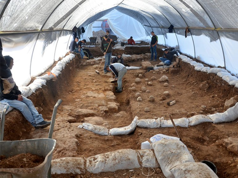 Workers slowly expose artifacts at the excavation site in the Russian Compound. Sling stones on the ground are evidence of the battle that was waged at the site 2,000 years ago. Photo by Yoli Shwartz, courtesy of the Israel Antiquities Authority.