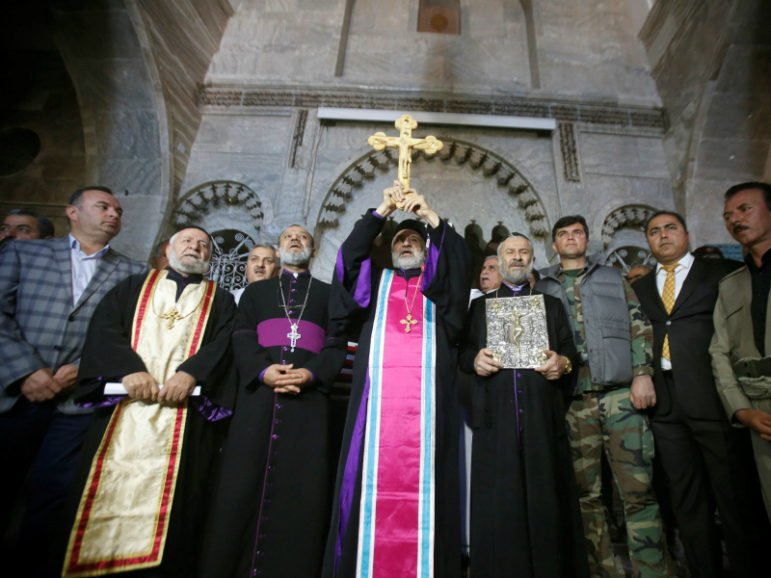 Iraqi Christians take part in a procession to erect a new cross over the Mar Korkeis church, after the original cross was destroyed by Islamic State militants, in the town of Bashiqa, Iraq, November 19, 2016.
