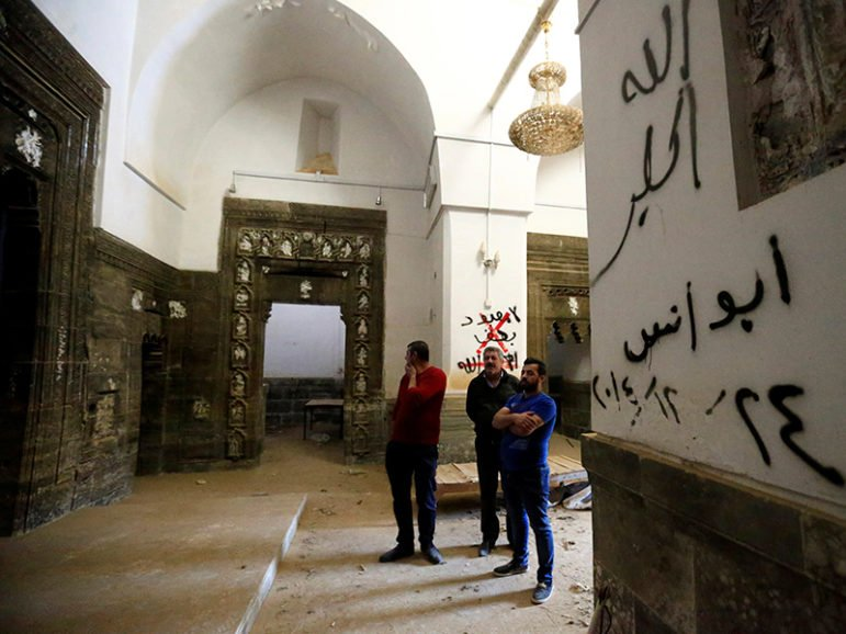 People inspect the Mar Behnam monastery after the town was recaptured from the Islamic State, in Ali Rash