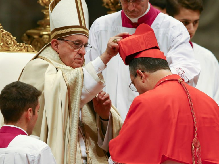 VATICAN CITY -- Pope Francis gives the traditional red biretta hat to a new cardinal, Sergio da Rocha of Brazil, during a ceremony to install 17 new cardinals in Saint Peter's Basilica at the Vatican, November 19, 2016. Photo via Reuters/Stefano Rellandini