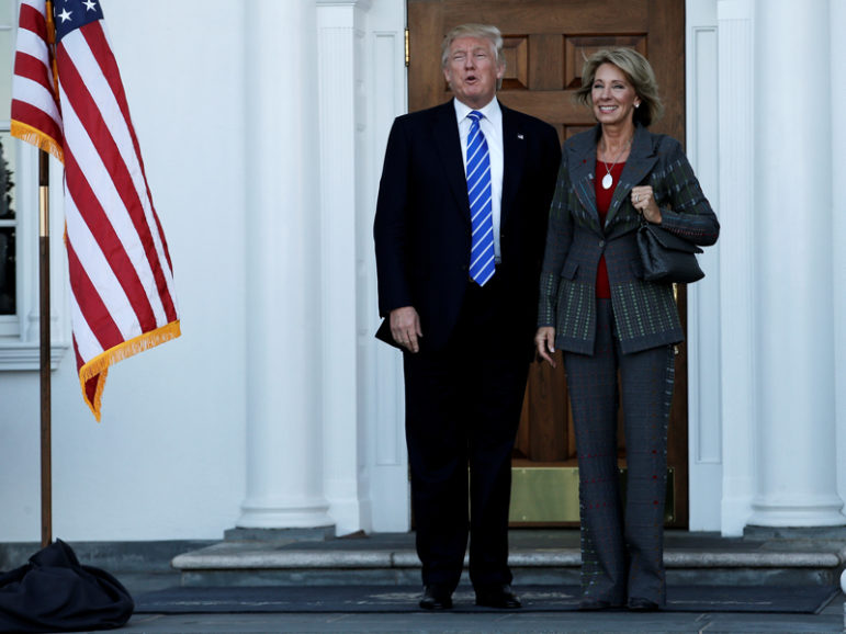 Then President-elect Donald Trump stands with Betsy DeVos after their meeting at the main clubhouse at Trump National Golf Club in Bedminster, N.J., on Nov. 19, 2016. Photo courtesy of Reuters/Mike Segar