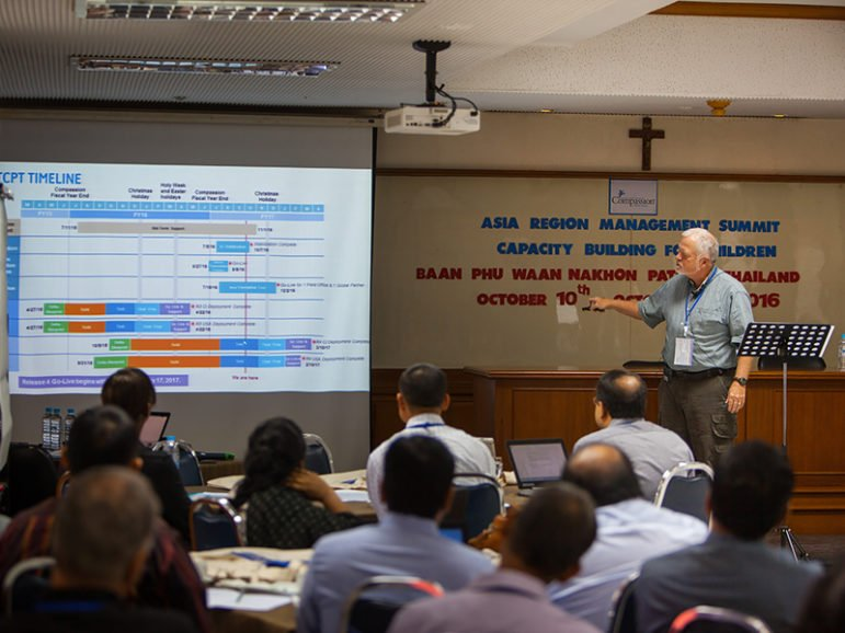 Ed Anderson, Compassion International's chief financial officer, discusses information systems with ministry workers in Thailand in October. The ministry's field offices in 26 countries work with nearly 2 million children. Photo courtesy of Compassion International
