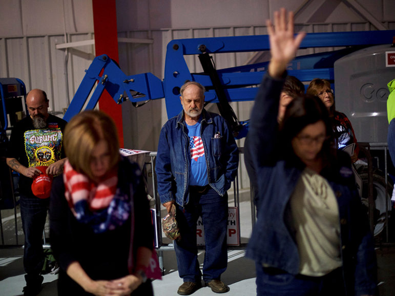 Supporters pray before Republican presidential nominee Donald Trump holds a rally at Atlantic Aviation in Moon, Pa., on Nov. 6, 2016. Photo courtesy of Reuters/Mark Makela *Editors: This photo may only be republished with RNS-ELECTION-PRAYERS, originally transmitted on Nov. 8, 2016.