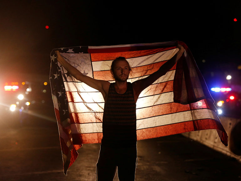 A protester holds a flag while in a group that took over the Hollywood 101 Freeway just north of Los Angeles City Hall on Nov. 9, 2016, in protest against  Donald Trump's win in the  presidential election. Photo courtesy of Reuters/Mario Anzuoni  *Editors: This photo may only be republished with RNS-FEA-OPED, originally transmitted on Nov. 10, 2016.