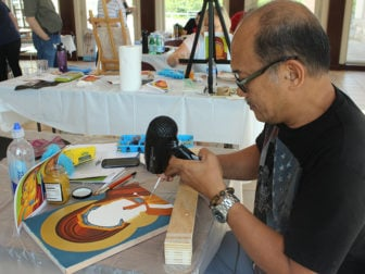 "Emmanuel ""Chito"" Santos"" works on an icon during a class at St. Sophia Greek Orthodox Cathedral in Washington, D.C. in June 2016. RNS photo by Adelle M. Banks"